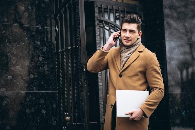 Giovane uomo d'affari in cappotto con il portatile fuori