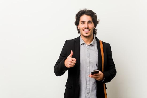 Giovane uomo d'affari in possesso di un telefono sorridente e alzando il pollice in su