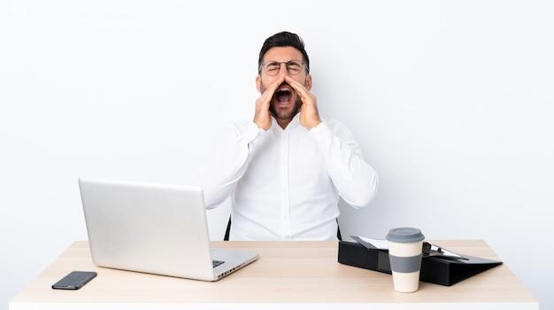 Giovane uomo d'affari in un posto di lavoro che grida e che annuncia qualcosa