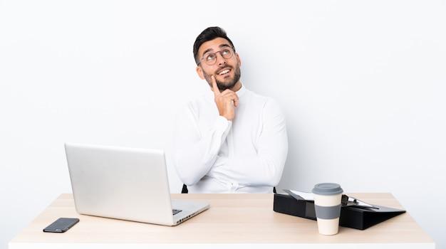 Giovane uomo d'affari in un posto di lavoro che pensa un'idea mentre osservando in su