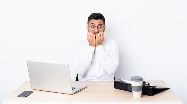 Giovane uomo d'affari in un posto di lavoro nervoso e spaventato mettendo le mani alla bocca