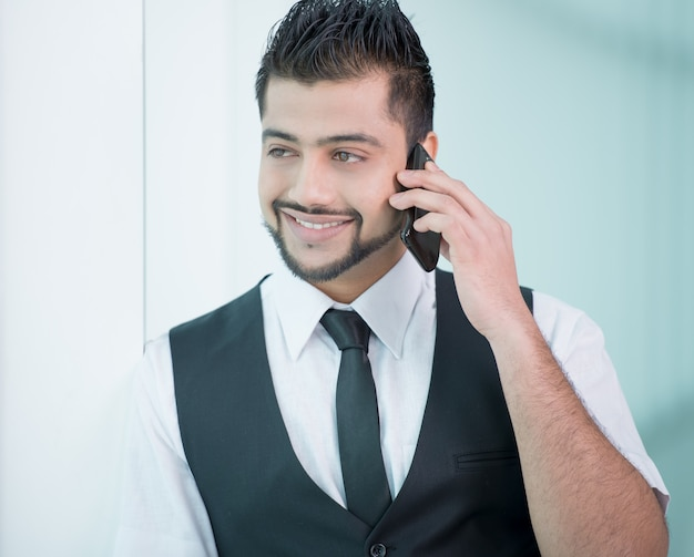 Giovane uomo d'affari indiano asiatico che sta sull'ufficio.