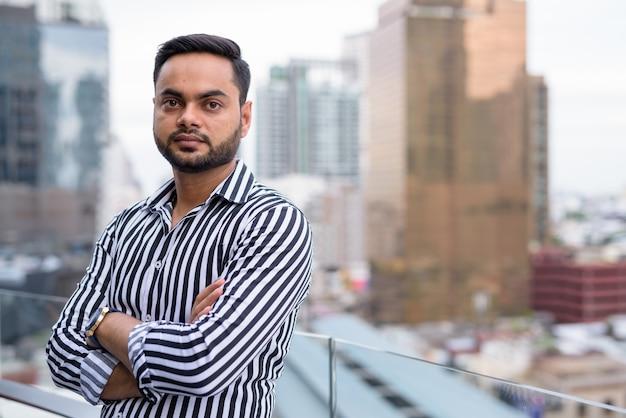Giovane uomo d'affari indiano barbuto contro la vista della città