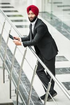 Giovane uomo d'affari indiano in ufficio moderno con la compressa.