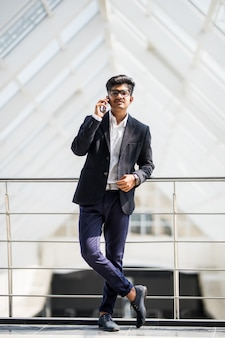 Giovane uomo d'affari indiano su un telefono al telefono