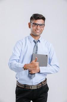 Giovane uomo d'affari indiano tenendo il quaderno e mostrando i colpi