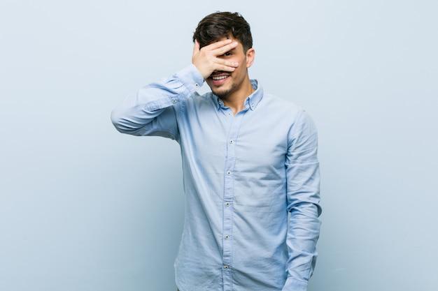 Giovane uomo d'affari ispanico battere le palpebre alla macchina fotografica con le dita, imbarazzato volto che copre.