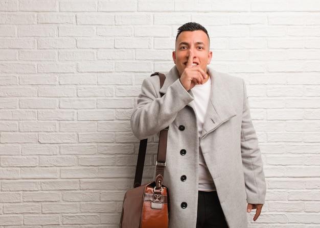 Giovane uomo d'affari latino mantenendo un segreto o chiedendo silenzio