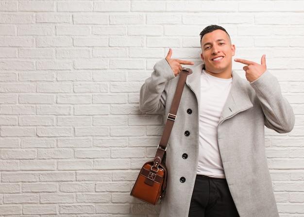 Giovane uomo d'affari latino sorride, indicando la bocca