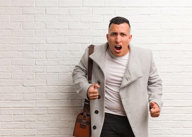Giovane uomo d'affari latino urlando molto arrabbiato e aggressivo