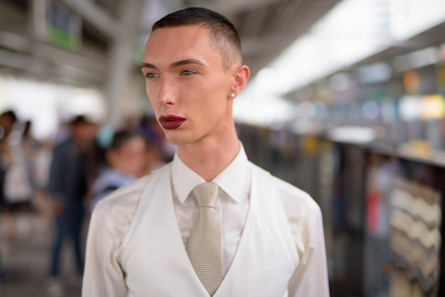 Giovane uomo d'affari lgtb omosessuale androgino che indossa il rossetto