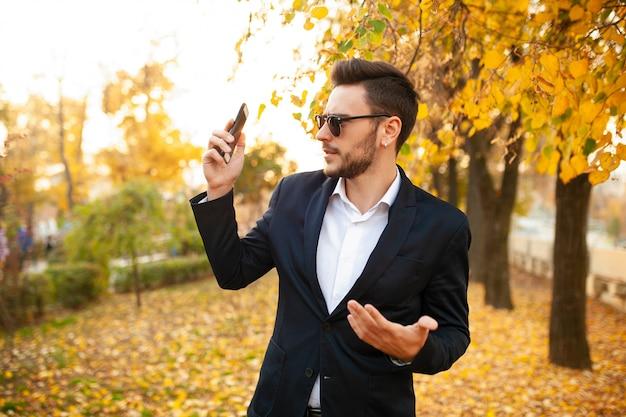 Giovane uomo d'affari maschio alla moda bello molto sorpreso dal telefono sgradevole