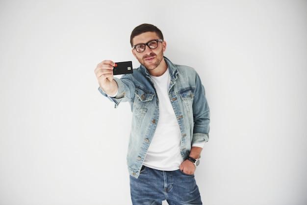 Giovane uomo d'affari maschio bello in abbigliamento casual in possesso di una carta di credito