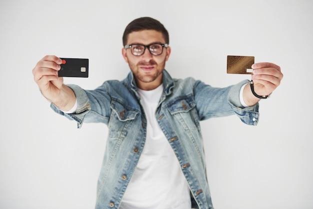 Giovane uomo d'affari maschio bello in abbigliamento casuale che tiene una carta di credito nelle tasche su bianco