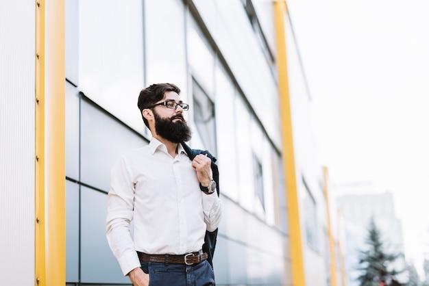 Giovane uomo d'affari moderno che si leva in piedi davanti alla costruzione corporativa