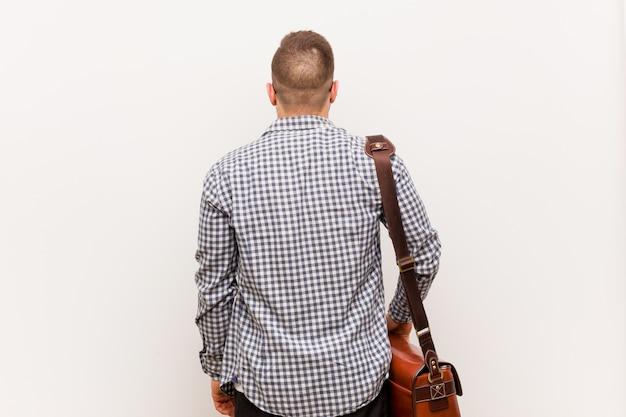 Giovane uomo d'affari moderno da dietro, guardando indietro.