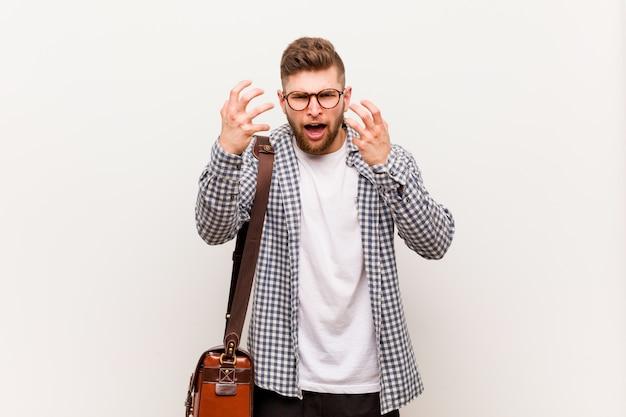 Giovane uomo d'affari moderno sconvolto urlando con le mani tese.