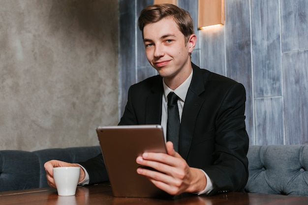 Giovane uomo d'affari nella compressa della tenuta dell'ufficio
