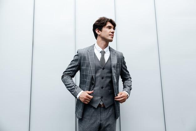 Giovane uomo d'affari nella posa della cravatta e del vestito