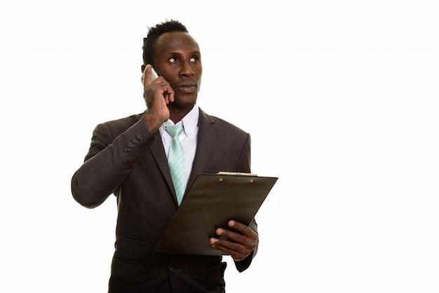 Giovane uomo d'affari nero africano premuroso che parla sul telefono cellulare