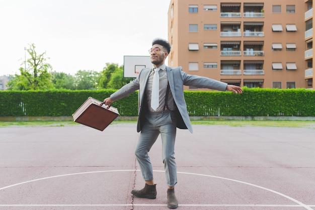 Giovane uomo d'affari nero all'aperto con le braccia spalancate sentirsi libero
