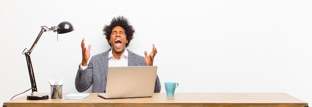 Giovane uomo d'affari nero che grida furiosamente, sentendosi stressato e infastidito con le mani in alto dicendo perché io su una scrivania