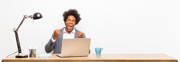 Giovane uomo d'affari nero che grida trionfalmente, ridendo e sentendosi felice ed eccitato mentre celebra il successo su una scrivania