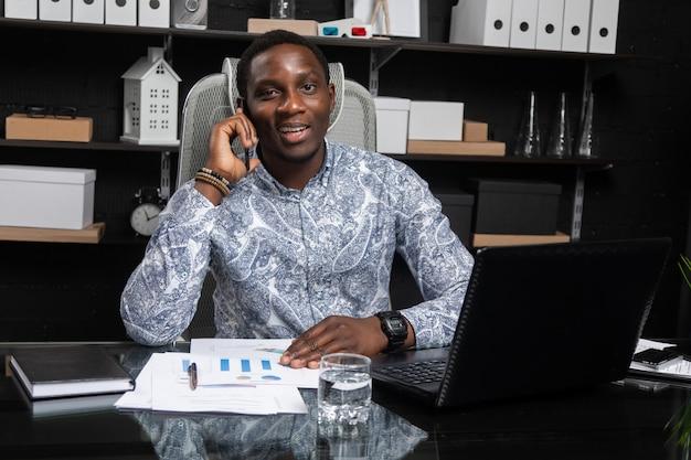Giovane uomo d'affari nero che parla sul telefono cellulare che si siede allo scrittorio del computer in ufficio