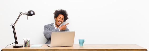 Giovane uomo d'affari nero che sembra eccitato e sorpreso indicando il lato e verso l'alto per copiare lo spazio