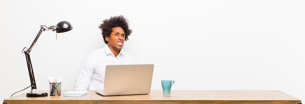 Giovane uomo d'affari nero che sembra preoccupato, stressato, ansioso e spaventato, in preda al panico e stringendo i denti su una scrivania