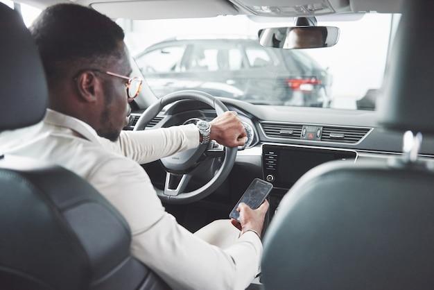 Giovane uomo d'affari nero prova su auto nuova. ricco uomo afroamericano.