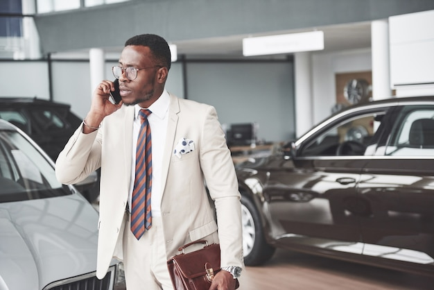 Giovane uomo d'affari nero sul fondo automatico del salone. concetto di vendita e affitto auto