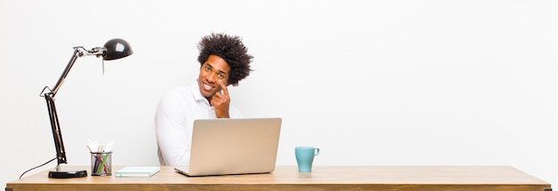Giovane uomo d'affari nero ti tiene d'occhio, non fidarti, guardare e stare all'erta e vigile su una scrivania