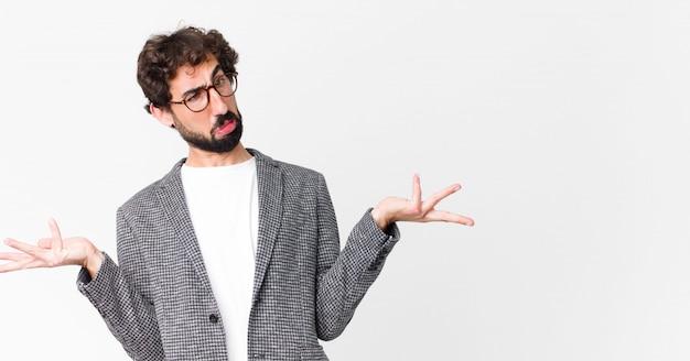 Giovane uomo d'affari pazzo che scrolla le spalle con un'espressione stupida, pazza, confusa, perplessa, sentendosi infastidito e all'oscuro sulla parete piatta