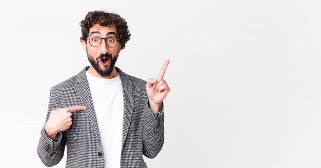 Giovane uomo d'affari pazzo che si sente orgoglioso e sorpreso, indicando con fiducia se stesso, sentendosi il numero uno di successo contro la parete piatta
