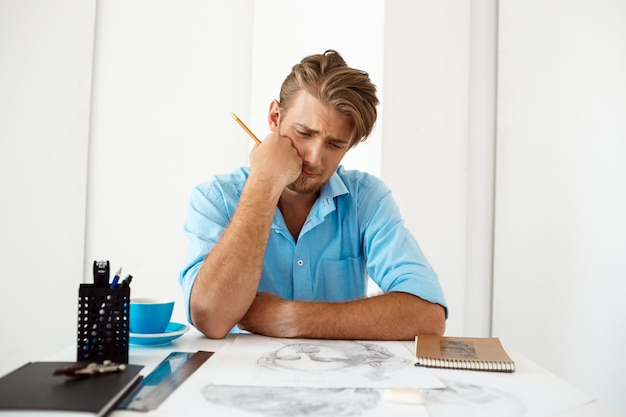 Giovane uomo d'affari pensieroso sicuro bello che si siede alla tavola che pensa sopra il ritratto del disegno a matita. interno di ufficio moderno bianco.