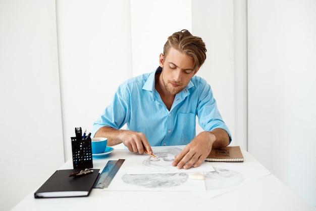 Giovane uomo d'affari pensieroso sicuro bello che si siede alla tavola con il ritratto del disegno a matita. interno di ufficio moderno bianco.