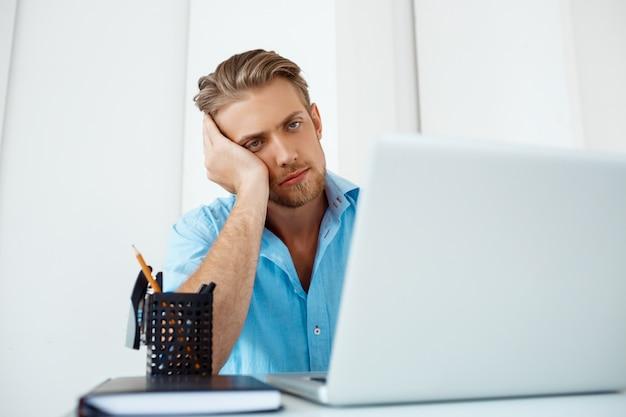Giovane uomo d'affari pensieroso sicuro stanco bello che si siede alla tavola che lavora al computer portatile con la tazza di caffè da parte. interno di ufficio moderno bianco