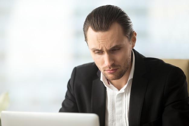 Giovane uomo d'affari perplesso che esamina lo schermo del computer portatile