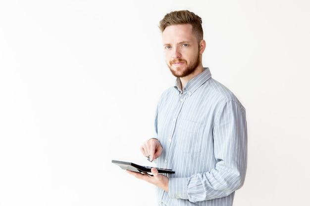 Giovane uomo d'affari positivo che conta sulla calcolatrice