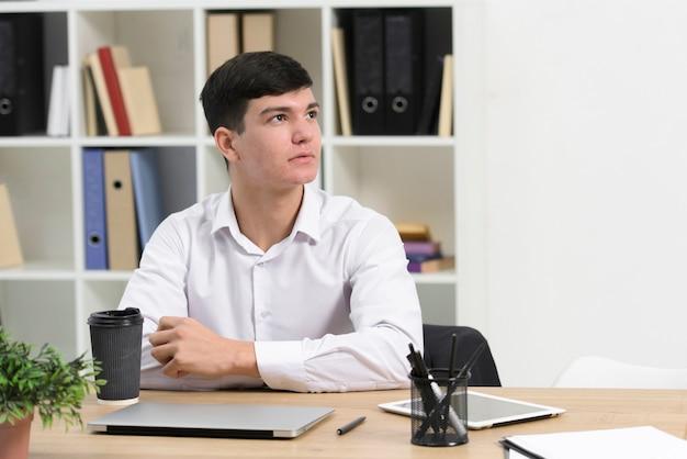 Giovane uomo d'affari premuroso che si siede allo scrittorio che osserva via