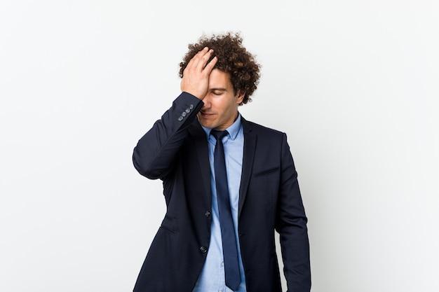 Giovane uomo d'affari riccio contro il muro bianco dimenticando qualcosa, schiaffeggiando la fronte con il palmo e chiudendo gli occhi.