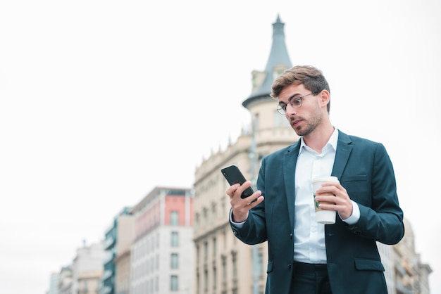 Giovane uomo d'affari scosso che esamina la tazza di caffè della tenuta dello smartphone a disposizione