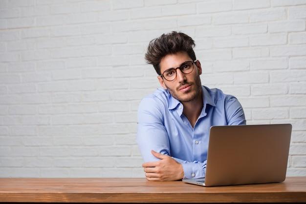 Giovane uomo d'affari seduto e lavora su un computer portatile allegro e con un grande sorriso