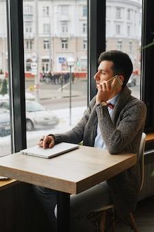 Giovane uomo d'affari serio che porta camicia blu che si siede in un caffè mentre parlando sul telefono distogli lo sguardo