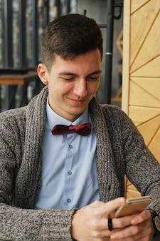 Giovane uomo d'affari serio che porta una camicia blu che si siede in un caffè mentre parlando sul telefono