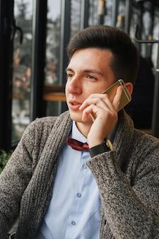 Giovane uomo d'affari serio che porta una camicia blu che si siede in un caffè