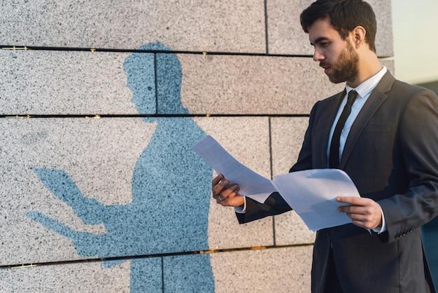 Giovane uomo d'affari serio del primo piano in un vestito classico che legge documen vantaggioso di affari