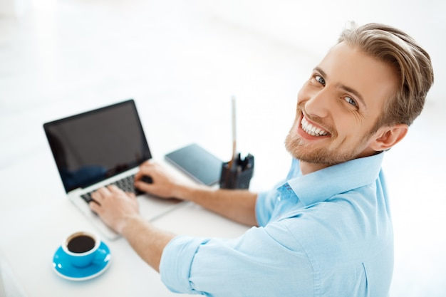 Giovane uomo d'affari sicuro allegro bello che si siede alla tavola che lavora al computer portatile con la tazza di caffè da parte. sorridente. interno di ufficio moderno bianco