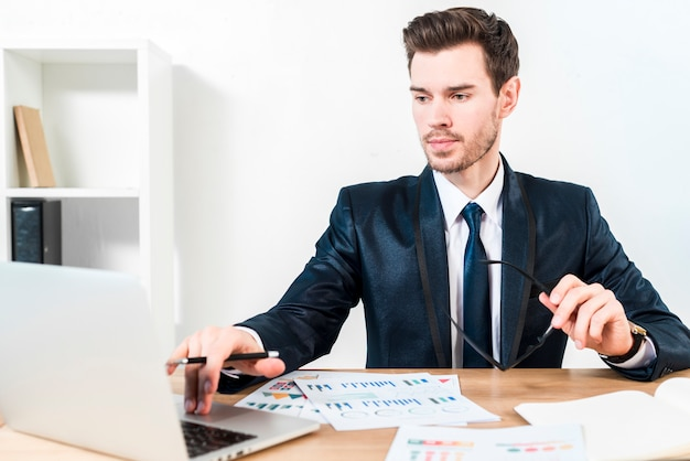Giovane uomo d'affari sicuro che utilizza il computer portatile nel luogo di lavoro nell'ufficio